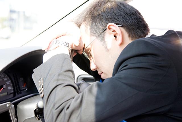車で仮眠を取る男性