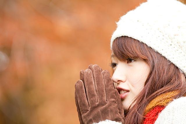 寒い冬に手を温める女性